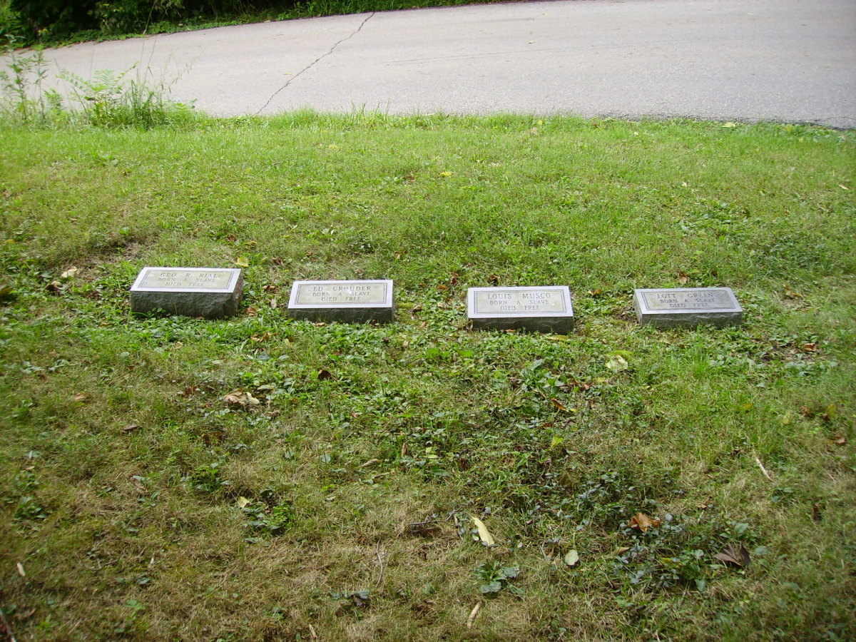 "Four of the five replaced headstones, bearing the names of the men, along with the words ""Born A Slave  Died Free"""