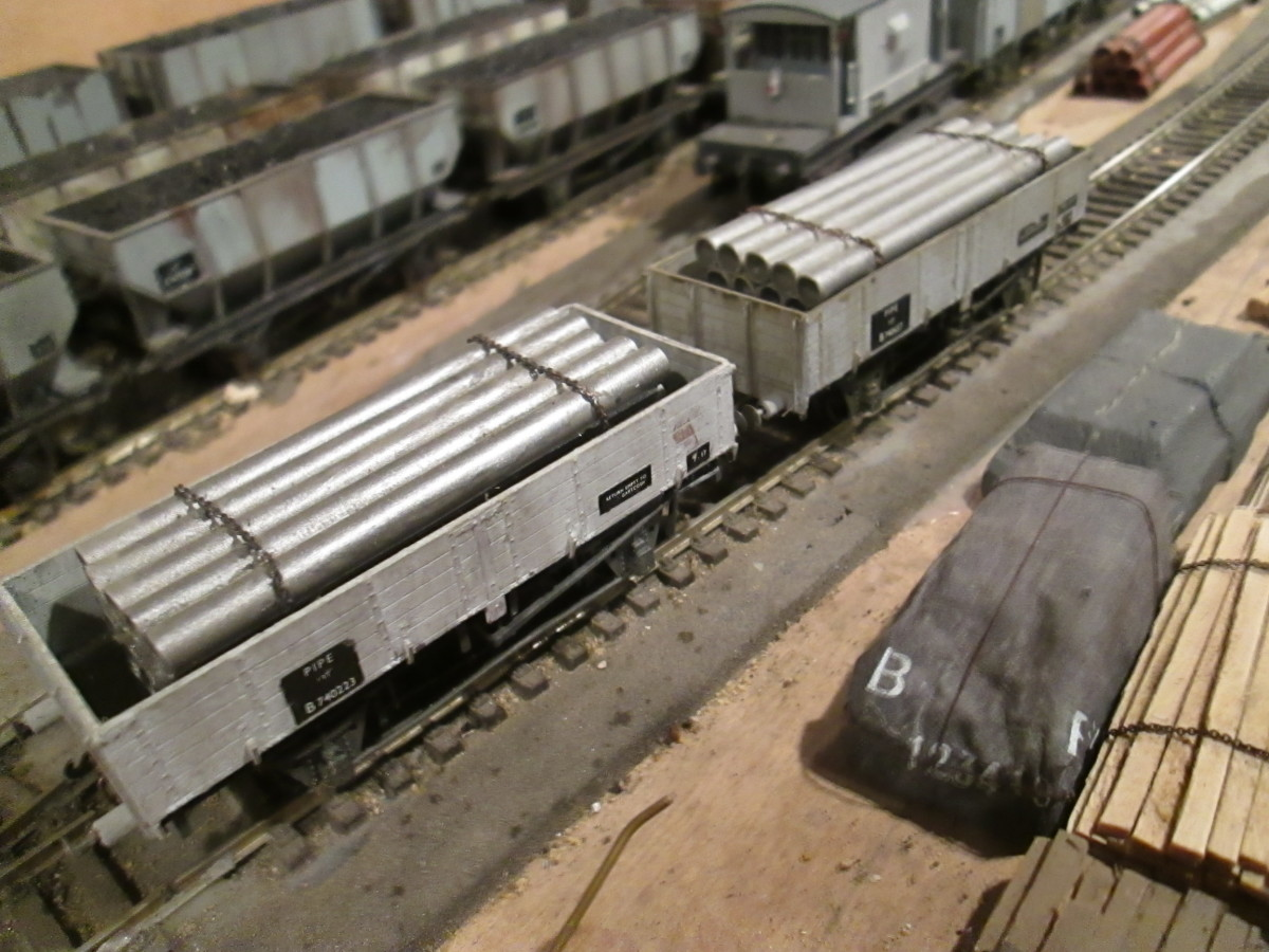 A pair of Parkside Pipe wagons with painted and chained plastic loads