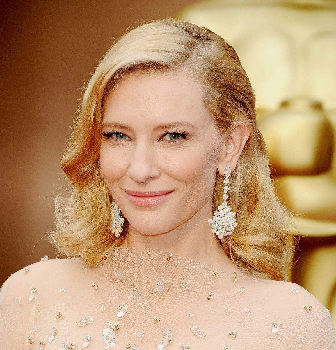 Cate Blanchett with light blonde hair and dangle earrings