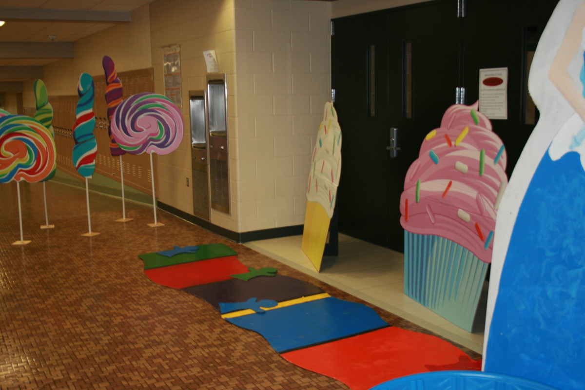 Candy Land game pieces, giant lollipops and cupcakes make for a great game board feel.