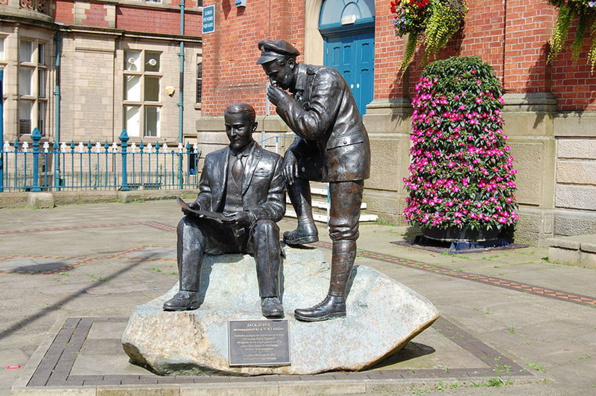 Jack Judge sits reading whilst a soldier looks over his shoulder.  Statue outside Victoria Market Hall in Stalybridge.
