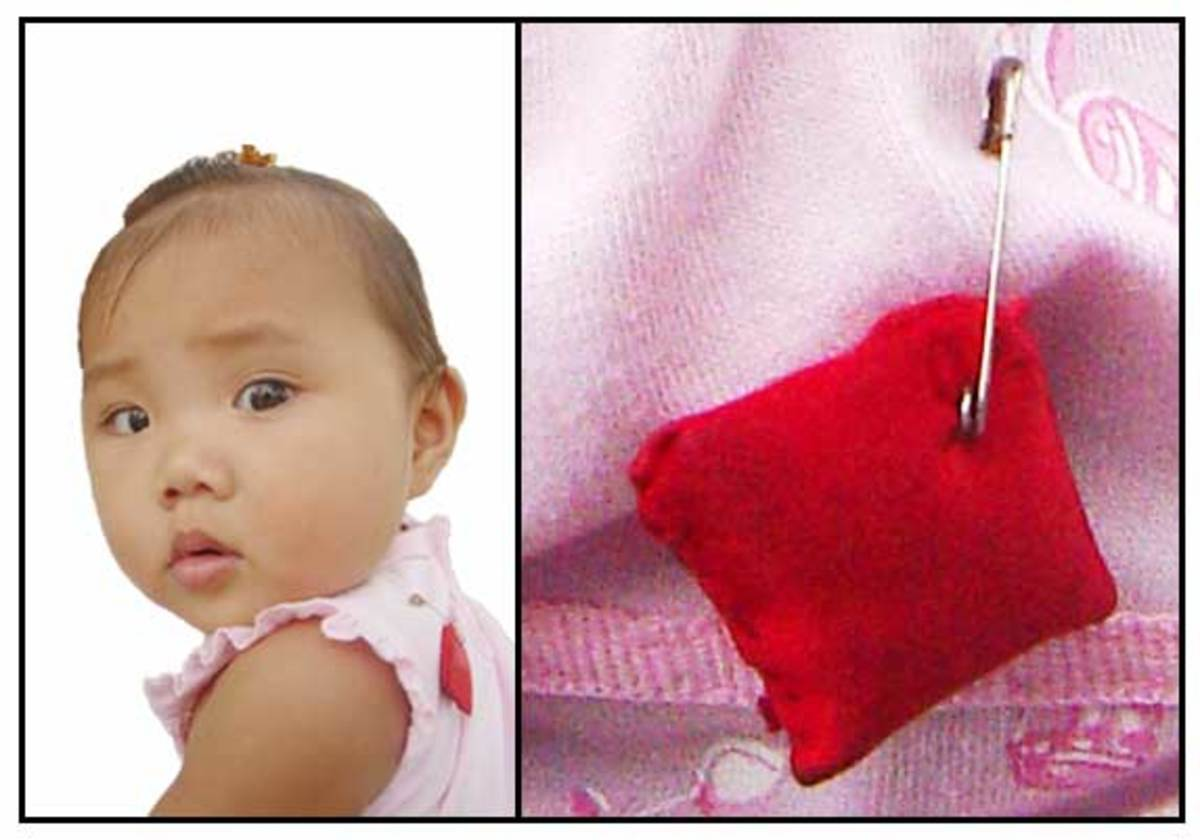 A charm pinned on clothes of babies is believed to ward off the greeting-induced malady called bati.