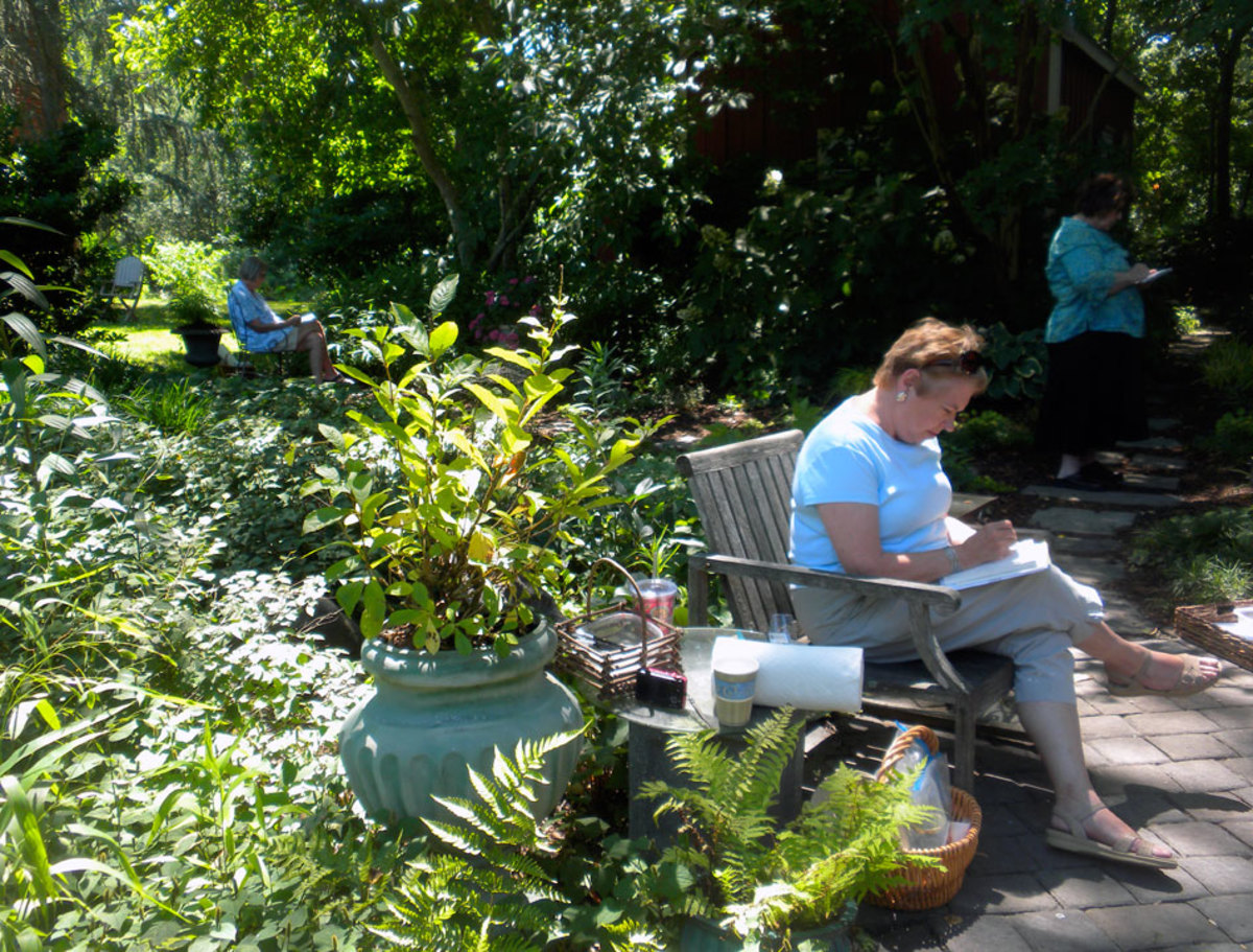 A student from the Waterview Gardens Workshop sits among the greenery as she sketches.