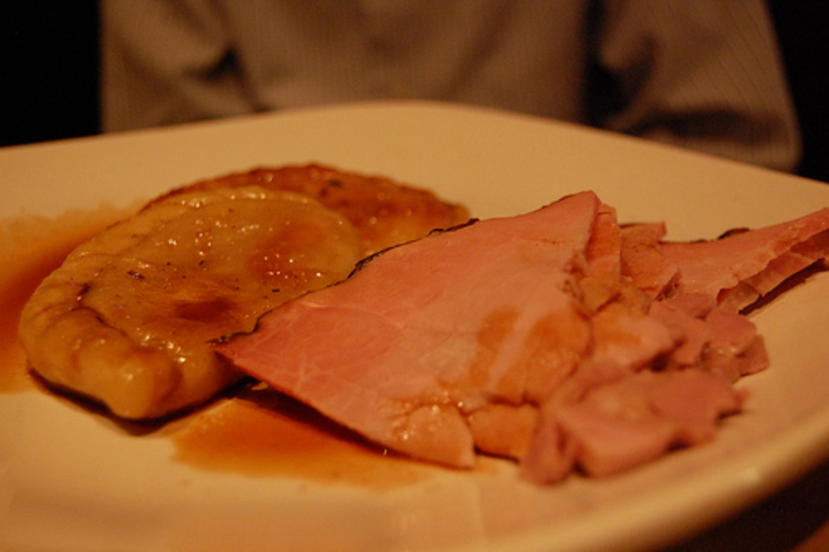 Slice of ham dressed with sauce, served with a pierogie.