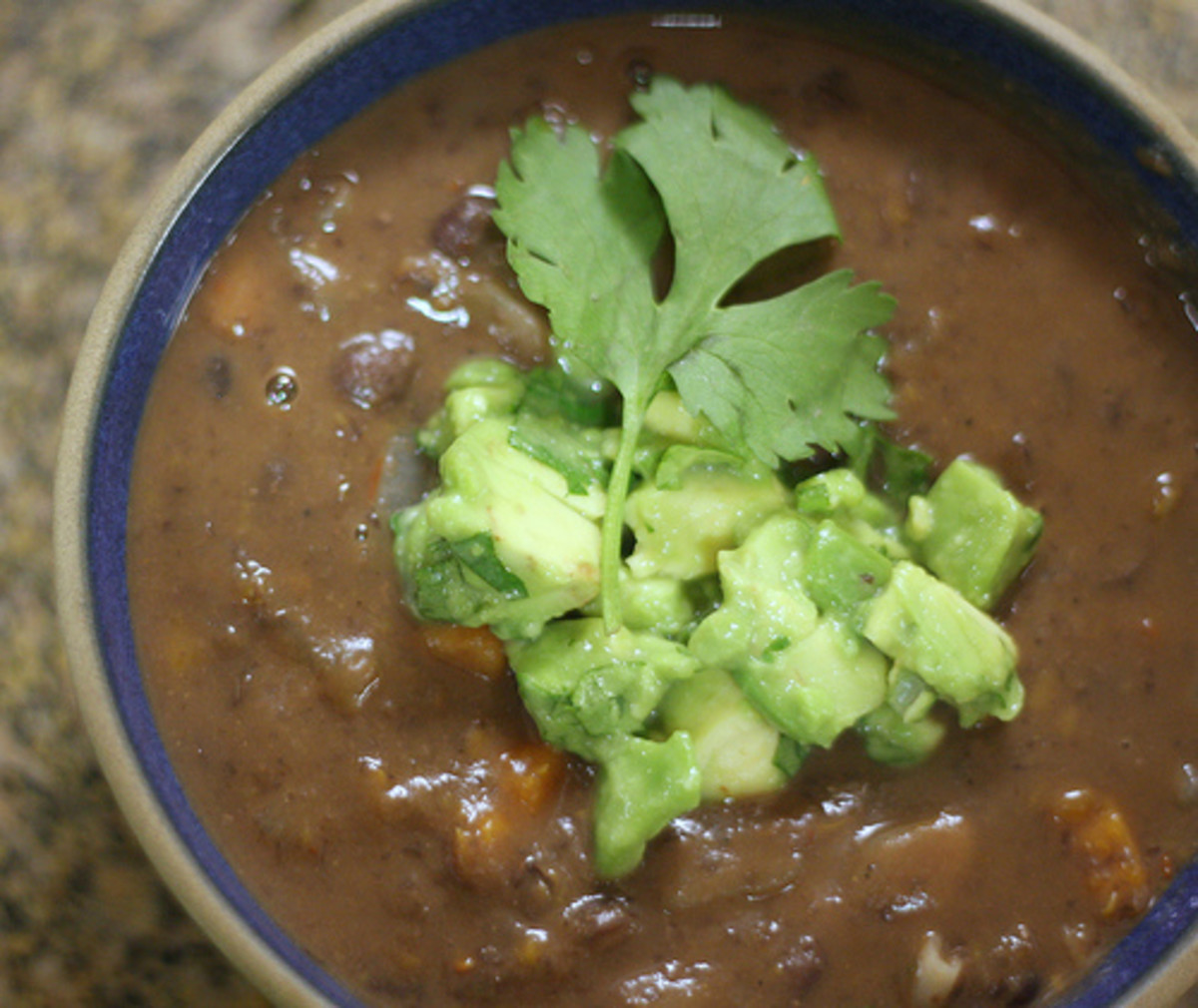 Add crushed tomatoes to make black bean soup. Serve with a guacamole garnish.