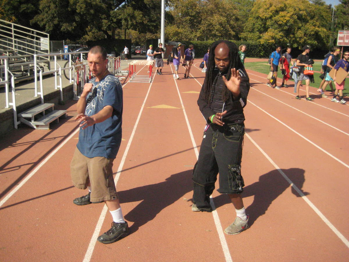 Jamie and Glenn step back into Neutral Bow stances. Note that their front toes are in line with their rear heels, as shown by the white lines on the track. Also note that their center-lines are covered by body angles and their hands.