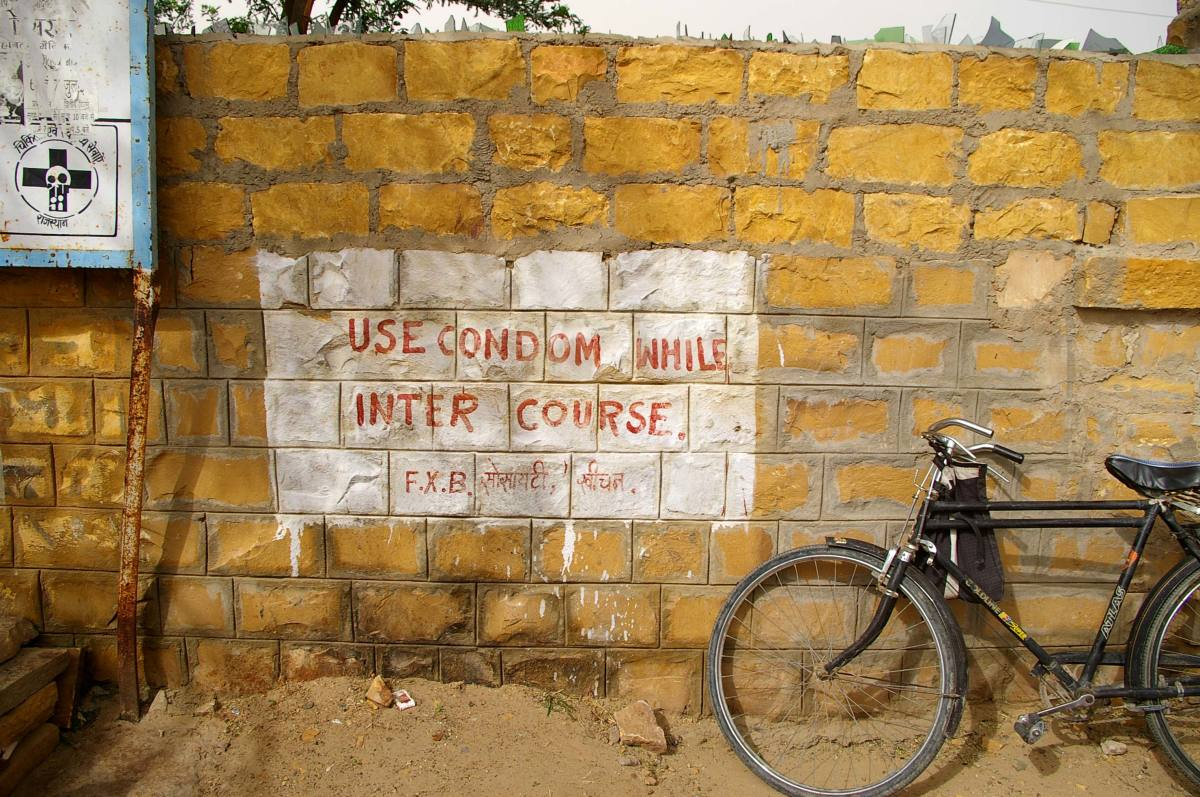 Public Service Announcement about using a condom and safe sex on a wall in India.