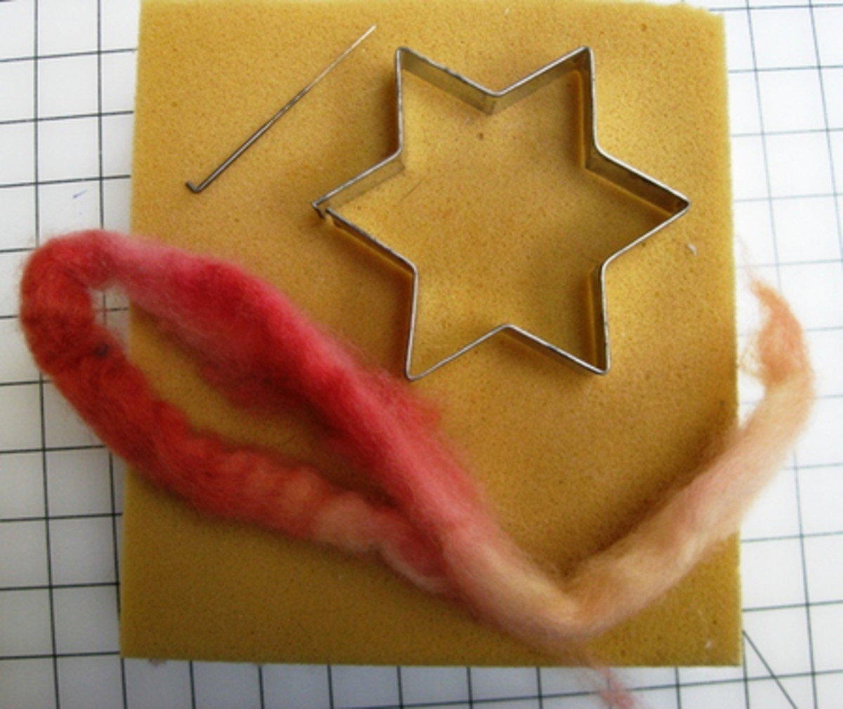 Needle felting supplies: felting needle, wool roving, cookie cutter, and foam pad for felting
