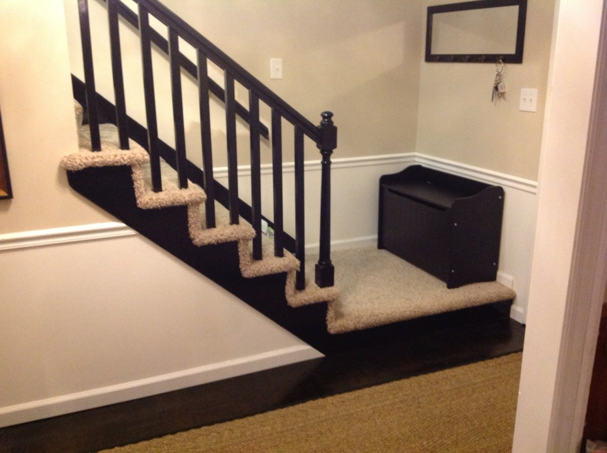 High gloss black railing along with storage bench for putting on your shoes as you grab your keys from one of the hooks above and head out the door.