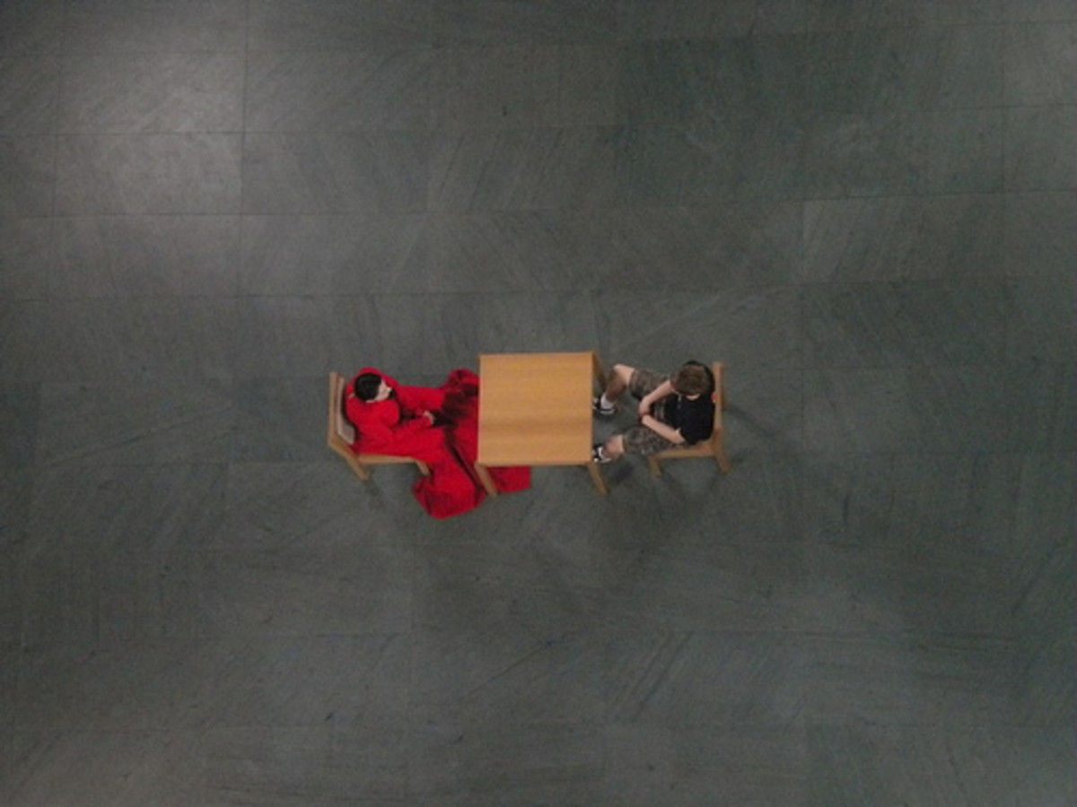 An aerial photograph of a moment from Marina Abramović's performance piece, The Artist is Present.