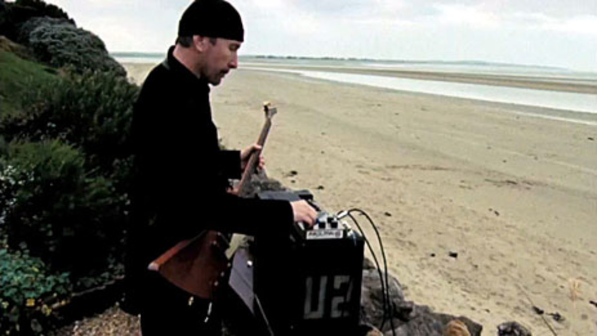 "The Edge adjusts a vintage EHX Deluxe Memory Man pedal in a scene from the film ""It Might Get Loud."""