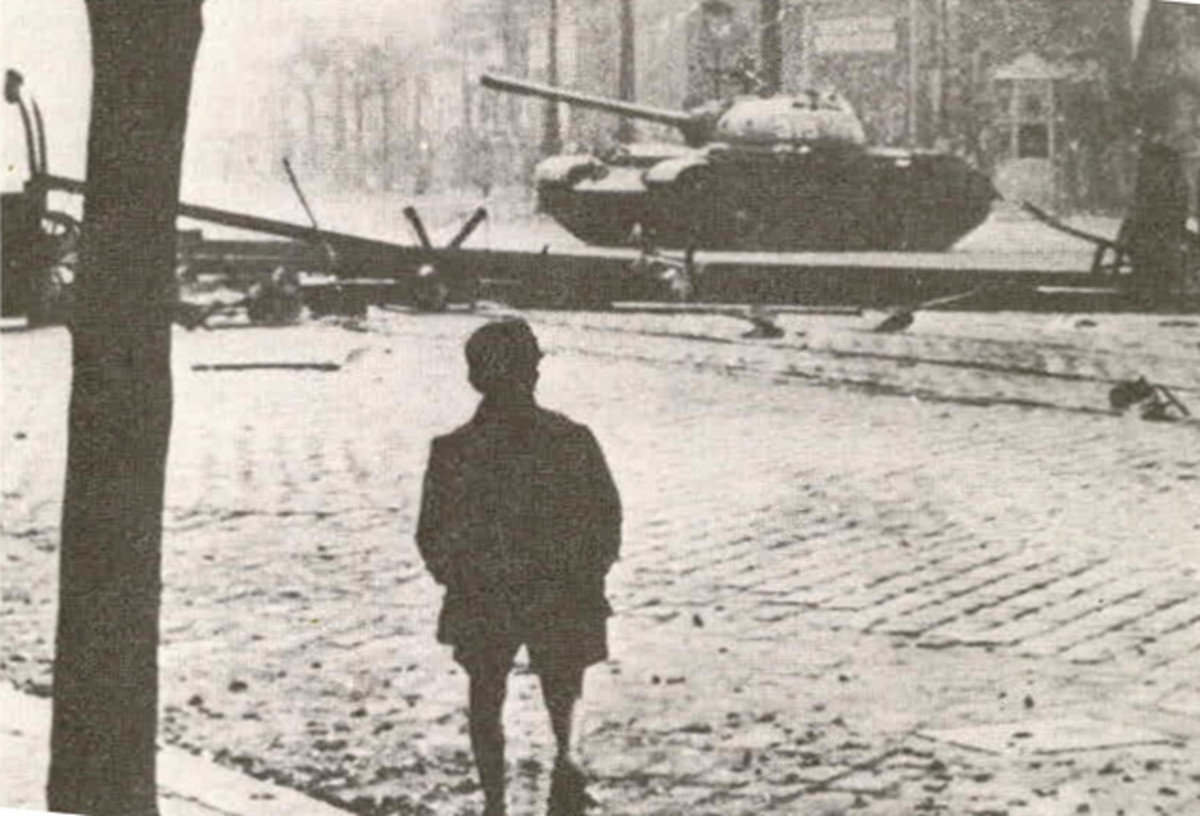 A young boy looks on as Soviet tanks suppress the Hungarian uprising.