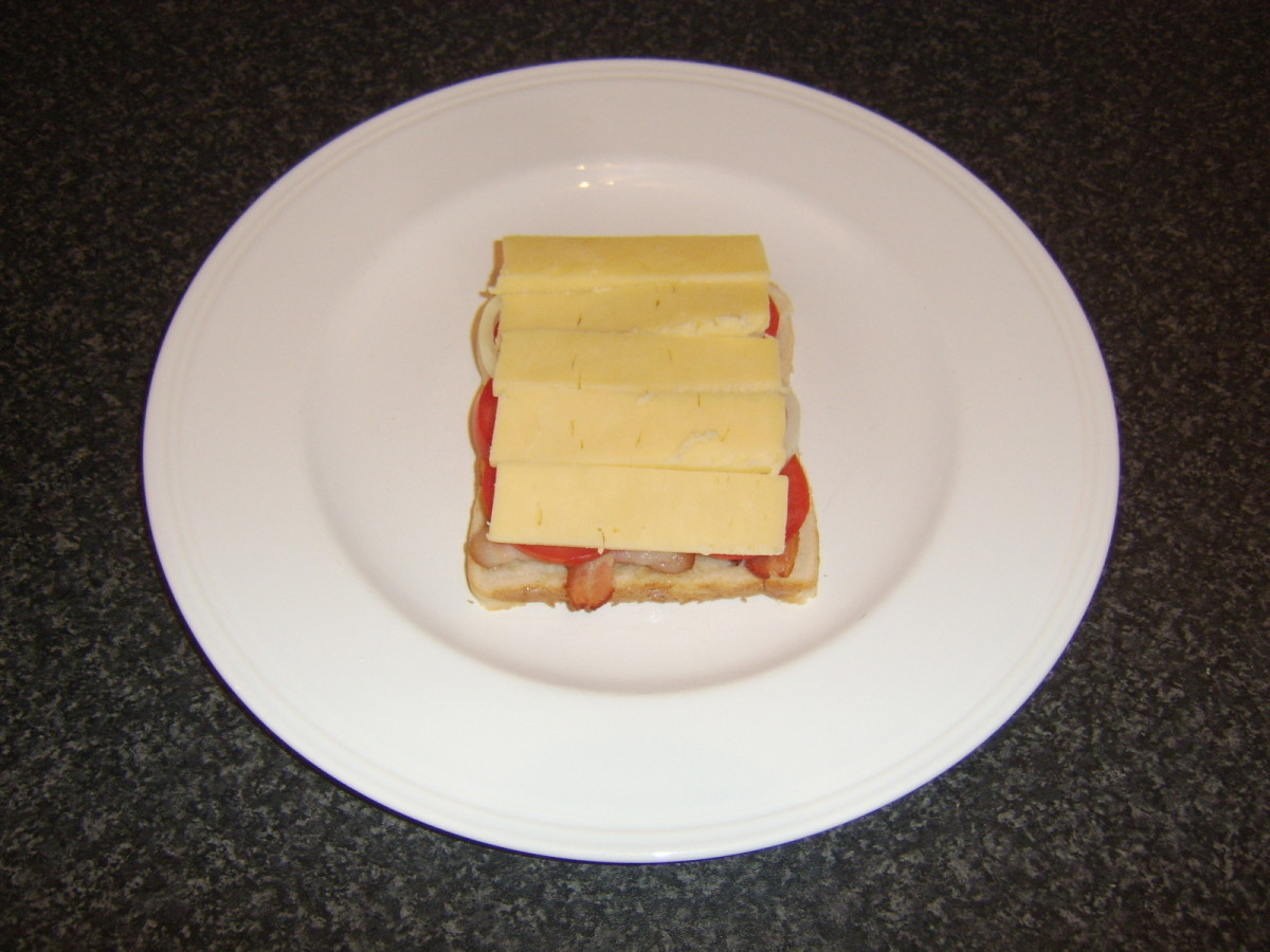 Cheese is placed on the sandwich which is now ready for grilling/broiling