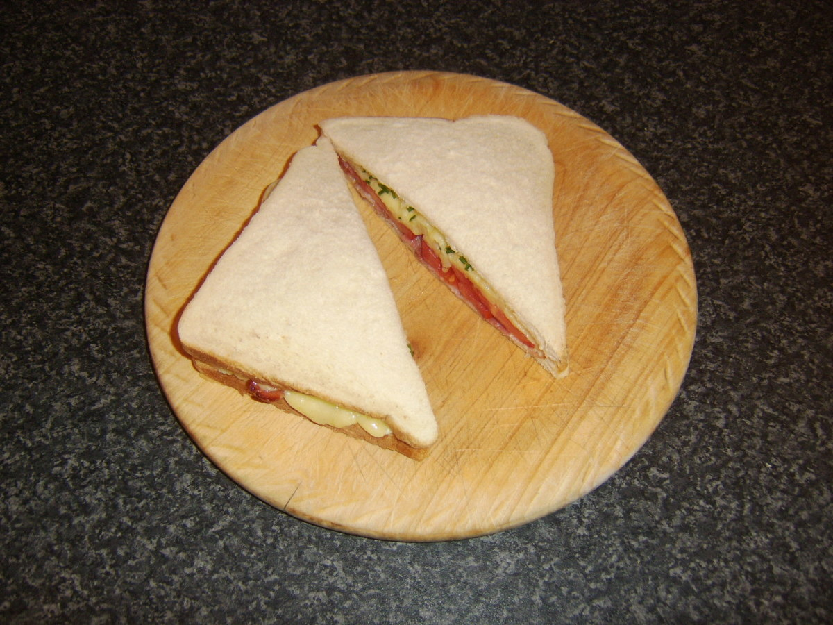 Bacon, tomato, onion and cheesse sandwich is sliced and ready to eat
