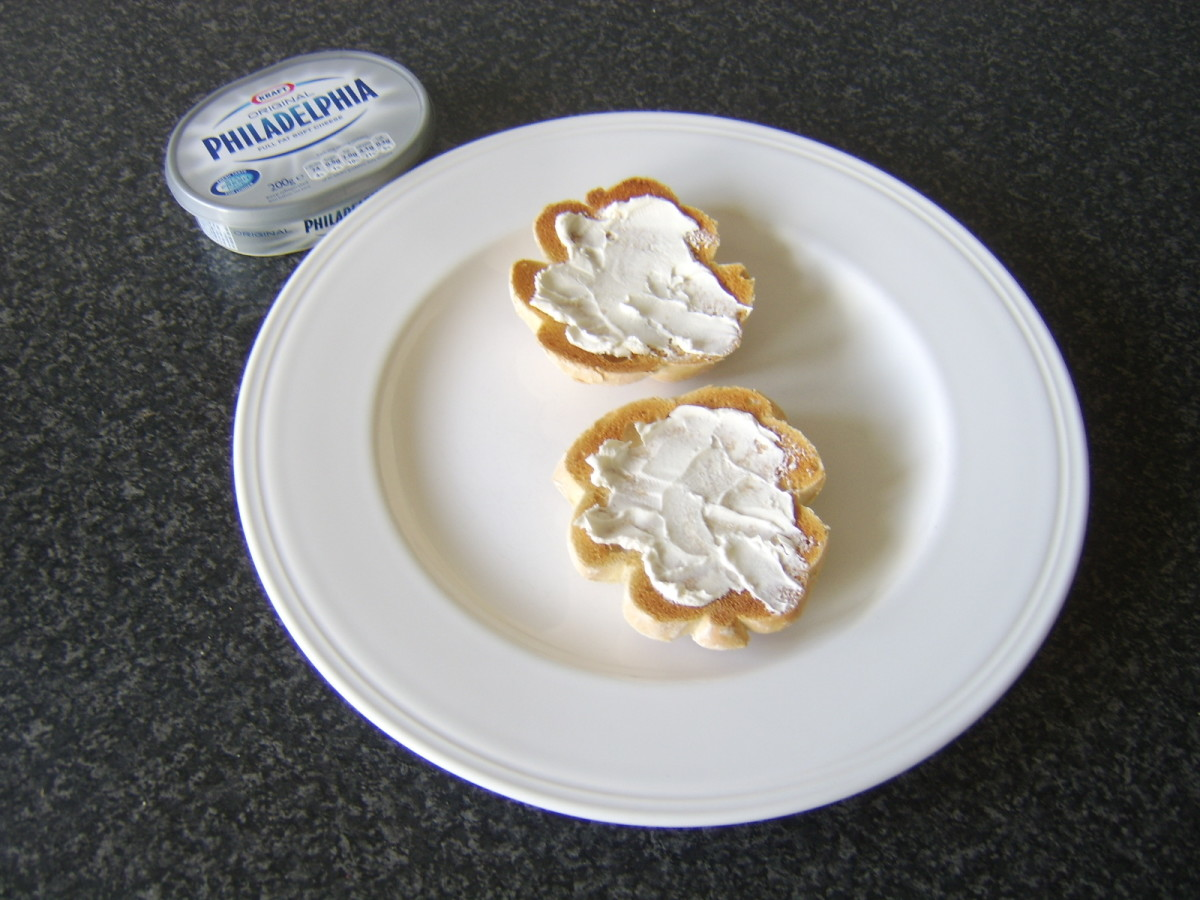 Cream cheese is spread on toasted roll