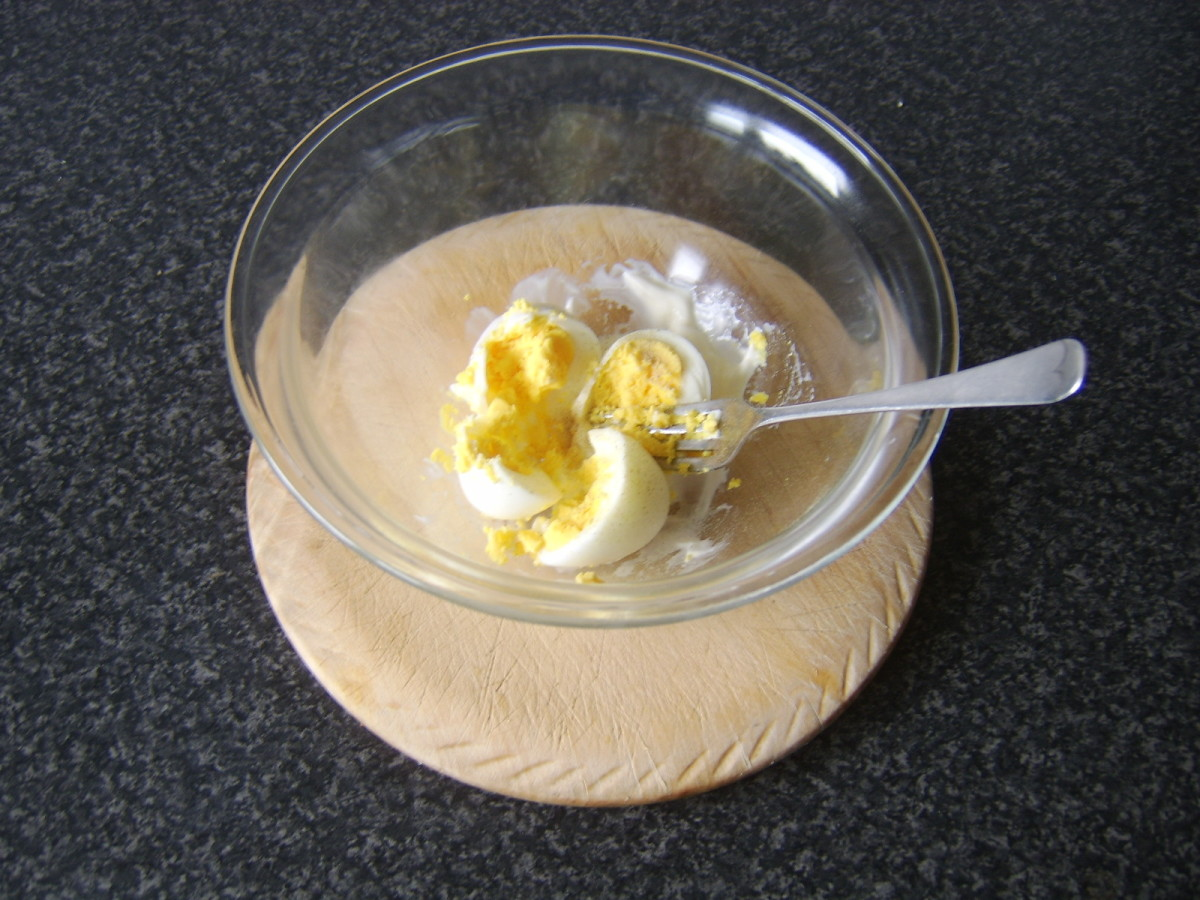 Hard boiled eggs are mashed with mayo and white pepper