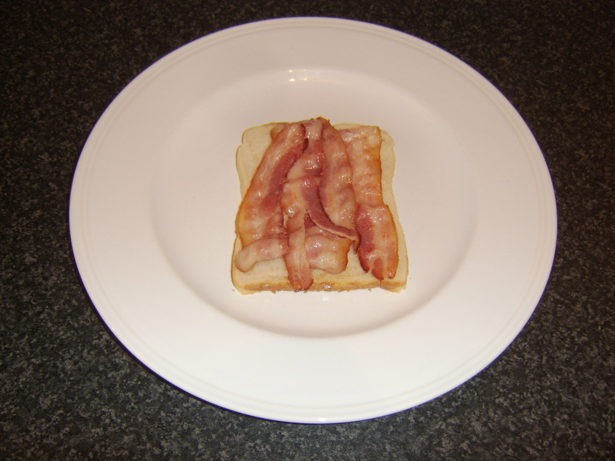 Bacon is laid on first slice of bread
