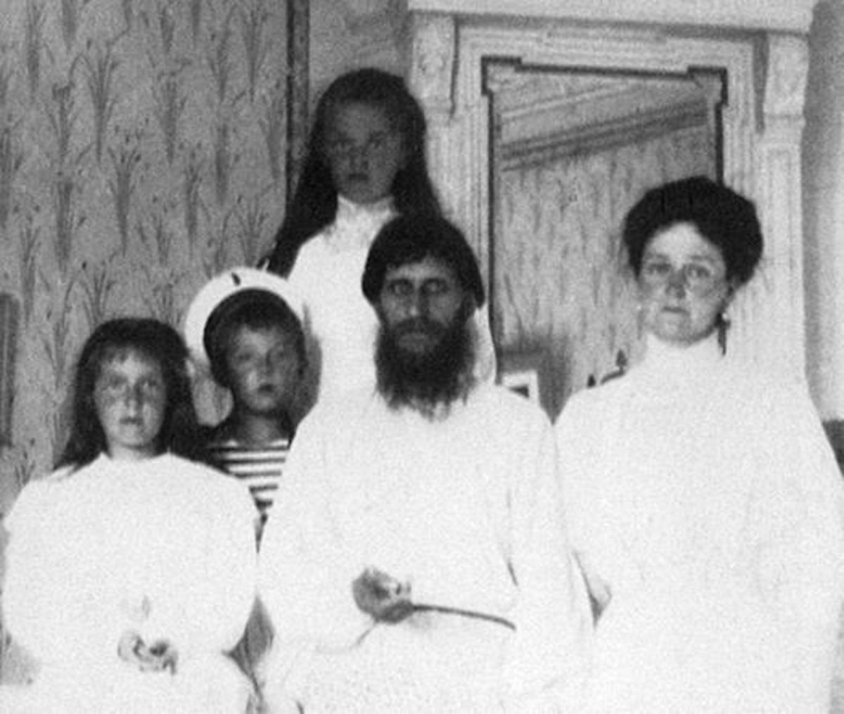 Rasputin with Tsarina Alexandra and Tsarevich Alexei on either side.