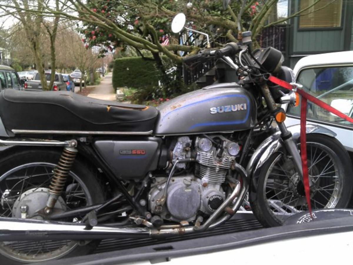 This neglected mid 70's Suzuki GS550 is in the back of a truck on it's way to a new home.