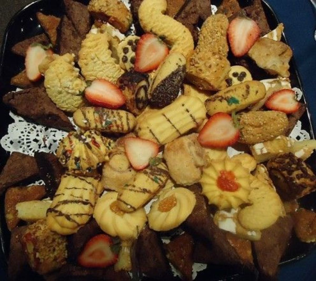 A variety of wedding cookies with strawberries.  Adding fresh fruit is a great way to enhance your wedding cookie table.