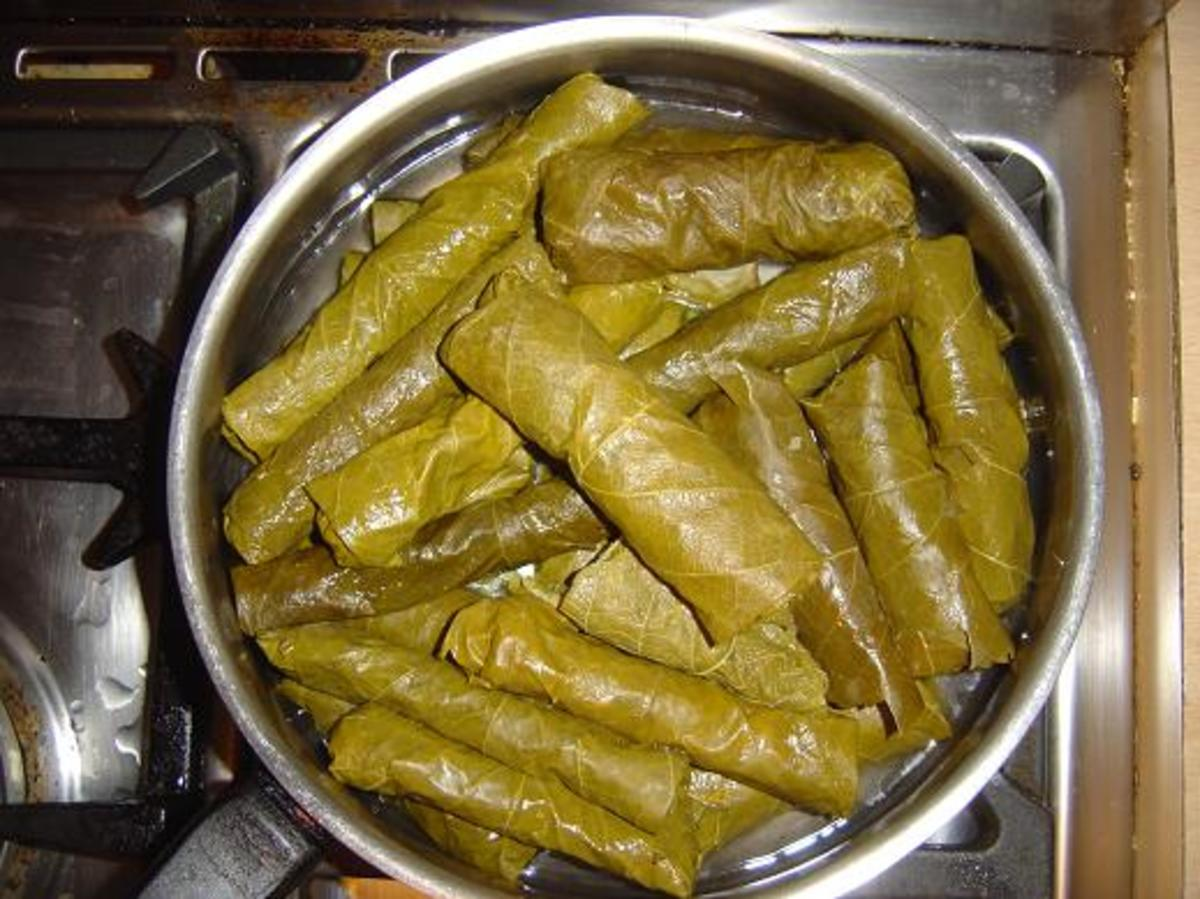 Place the stuffed vine leaf rolls into a sauté pan or saucepan and simmer