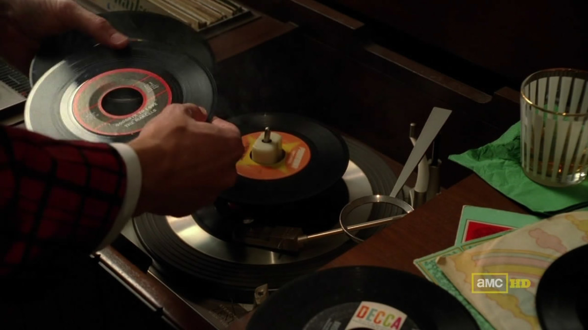 A Mad Men Character Putting On A Record