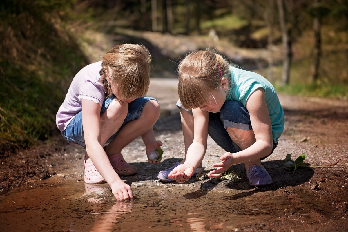 Constructing a fairy garden entices children outdoors. Here, the girls are finding smooth pebbles to make a path in their miniature garden.