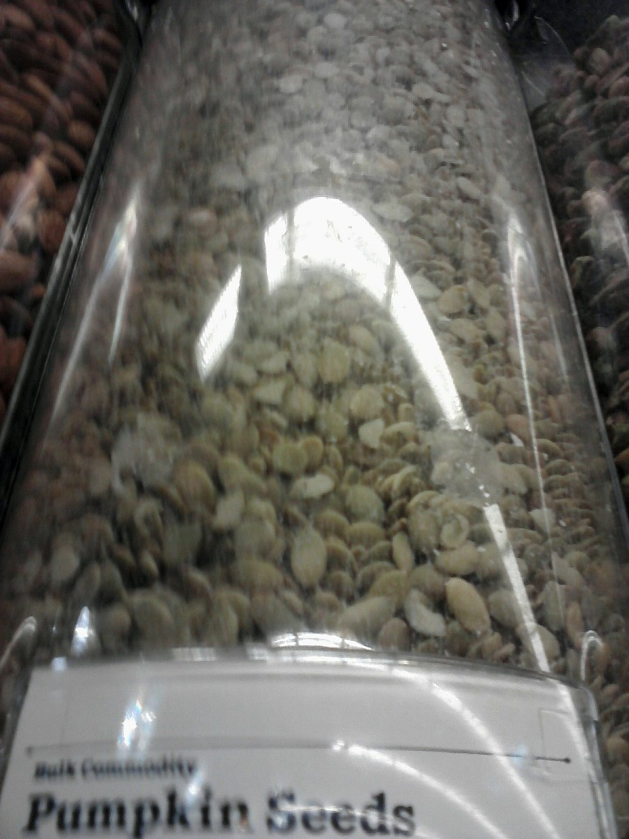 Shelled pumpkin seeds in dispenser.