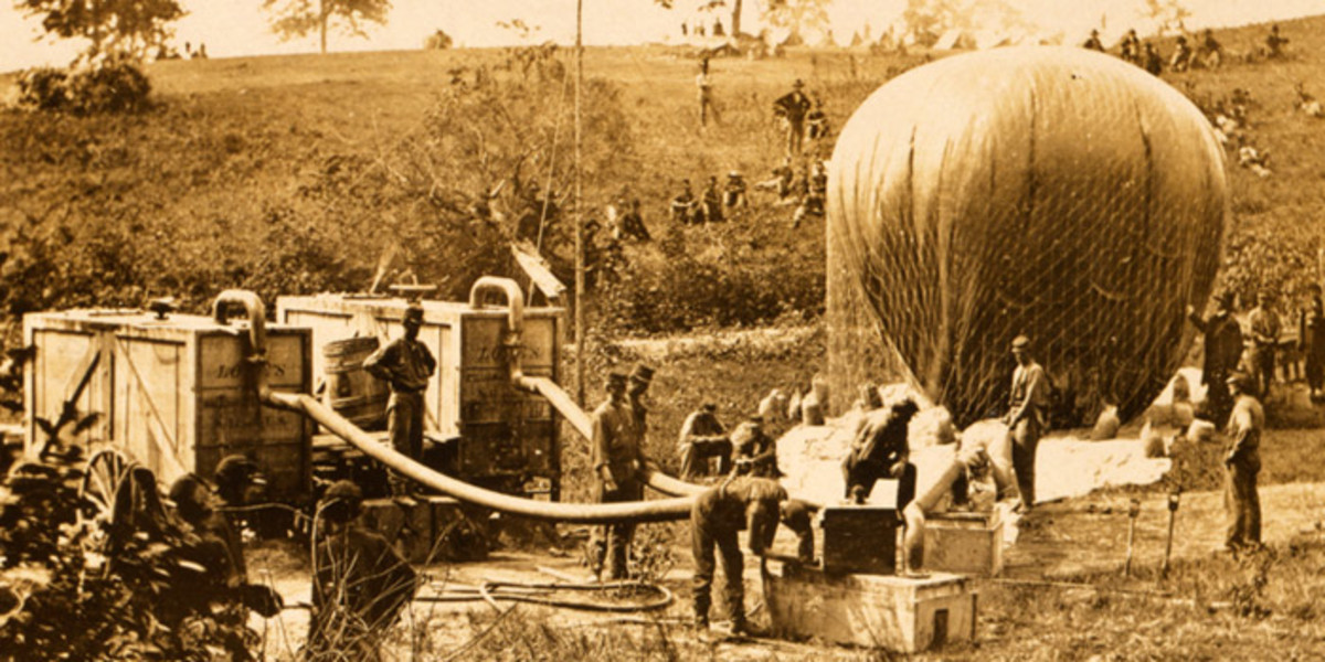 A balloon is inflated. Note the wagons to the left that provided the inflation