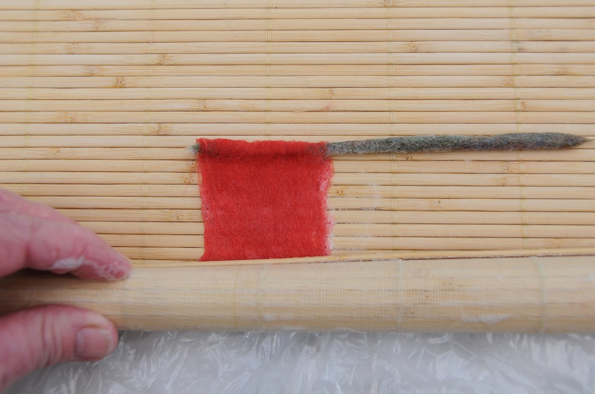 Roll the center bud of the rose inside  the sushi mat, Include the pipe cleaner once the lower end has been felted.