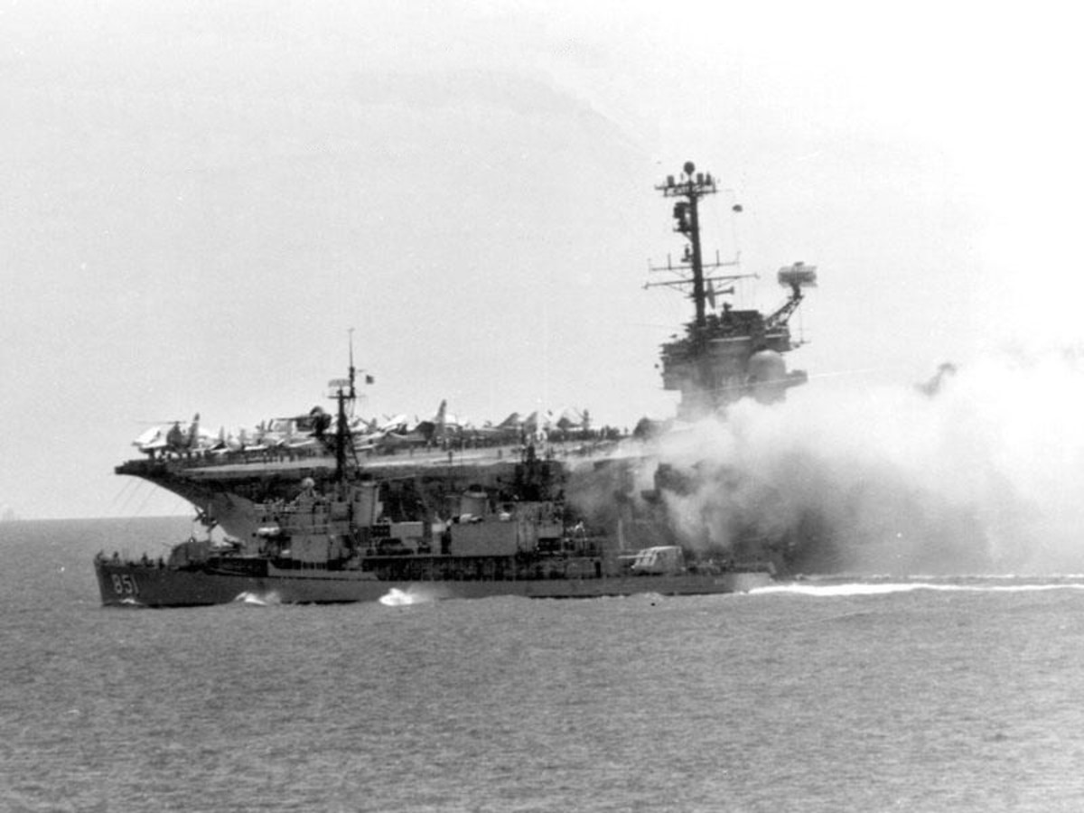 USS Forrestal on fire, the worst US carrier fire since WWII; USS Rupertus (DD-851) maneuvers to within 20 ft (6.1 m) to use fire hoses.
