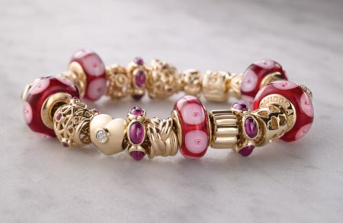 beautiful story book pink and fuscia and gold Pandora bracelet complete with intricate charms of hearts and murano glass
