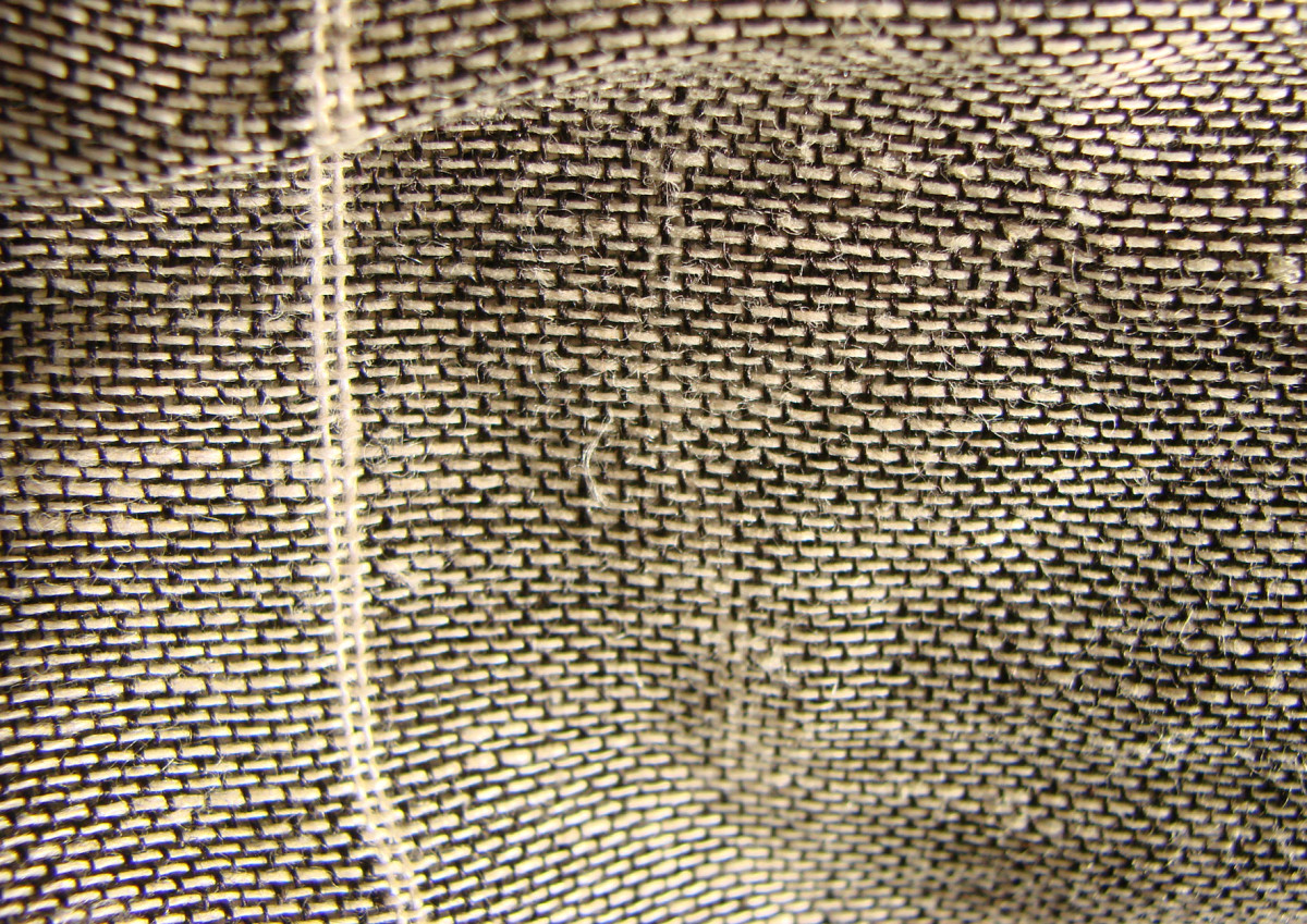 This close up shows the vertical threads, called the warp and the horizontal threads called the weft.