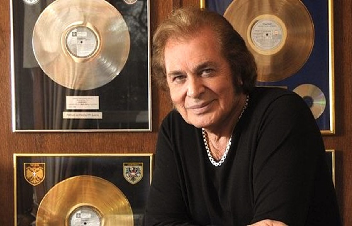 Engelbert Humperdinck in 2013 posing in front of his wall of gold and platinum records.