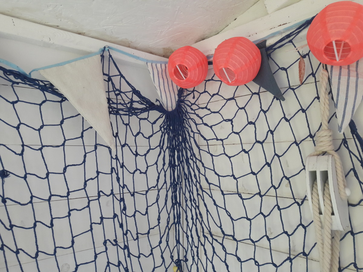 Fishing net with pink lights in a beach hut themed summerhouse.
