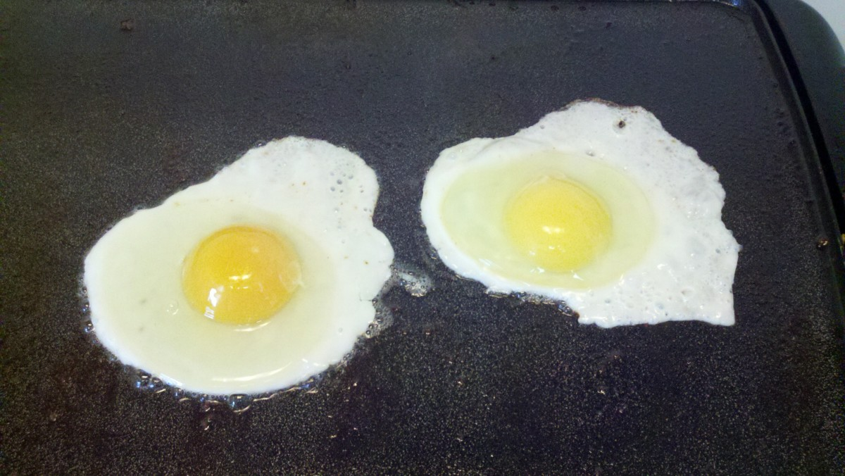 One of our eggs frying on the left next to a store one on the right.  See the difference in yolk color?