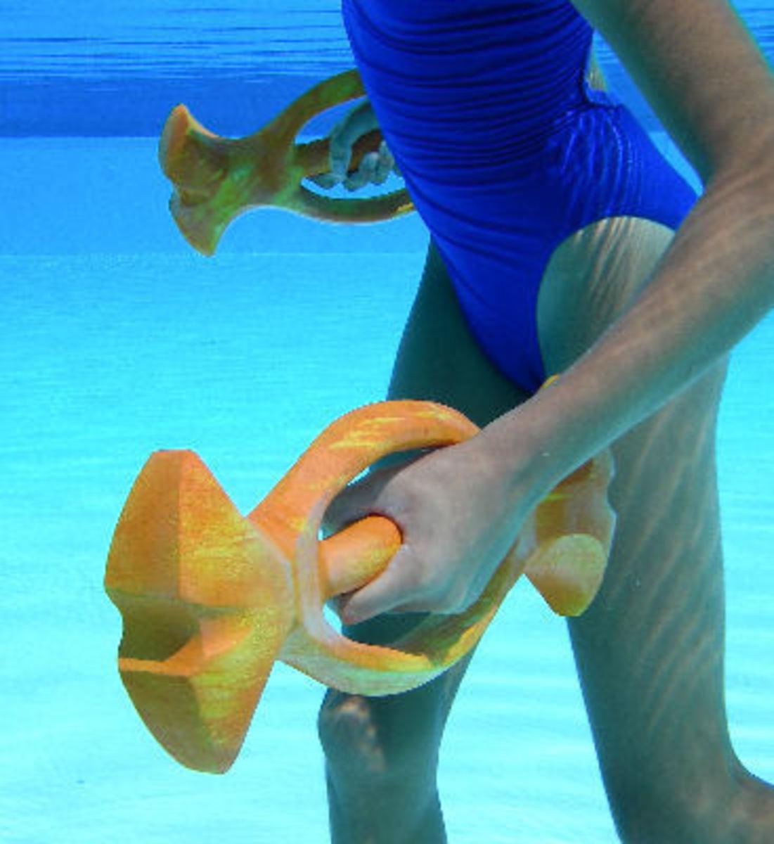 woman in blue swim suit using orange ergonomic barbells
