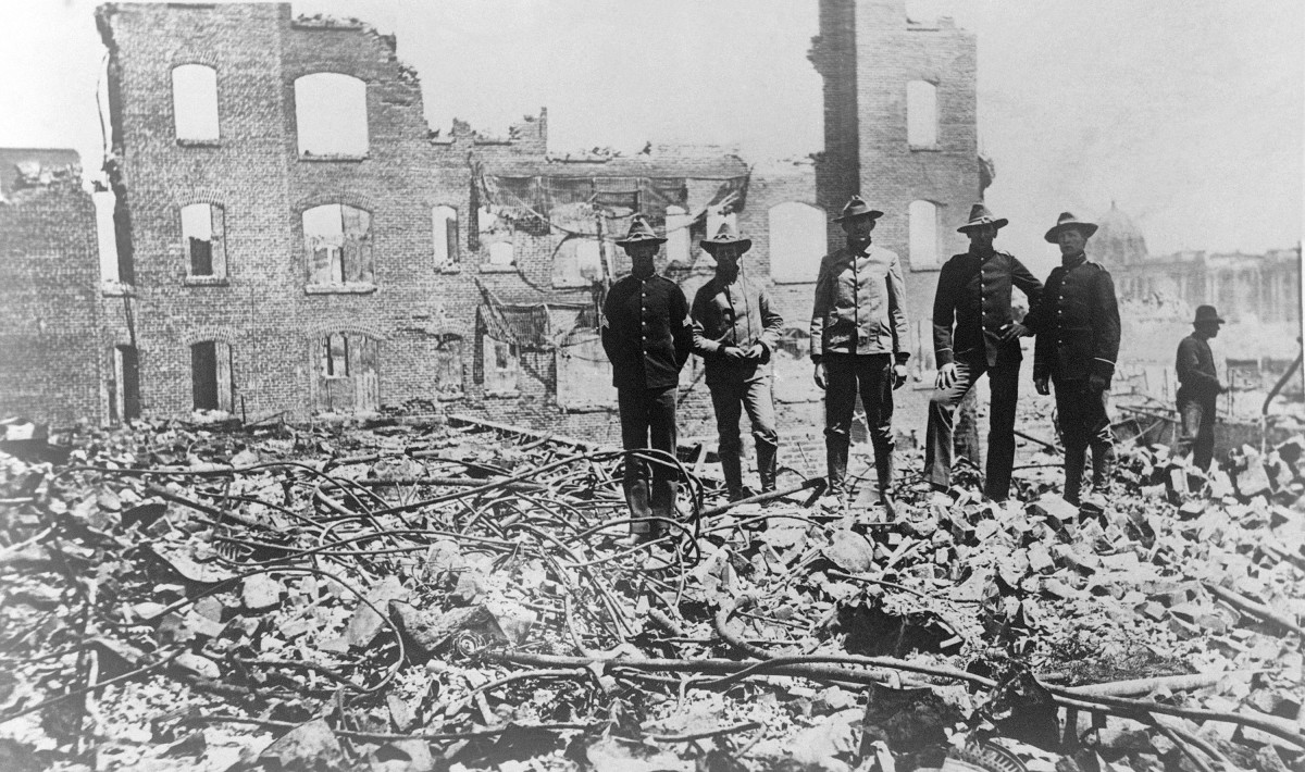 Soldiers in San Francisco 1906 ruins.  Soldiers from the Presidio stand amid the rubble of fallen buildings after the earthquake. The Hall of Records (dome) is in the background (right).