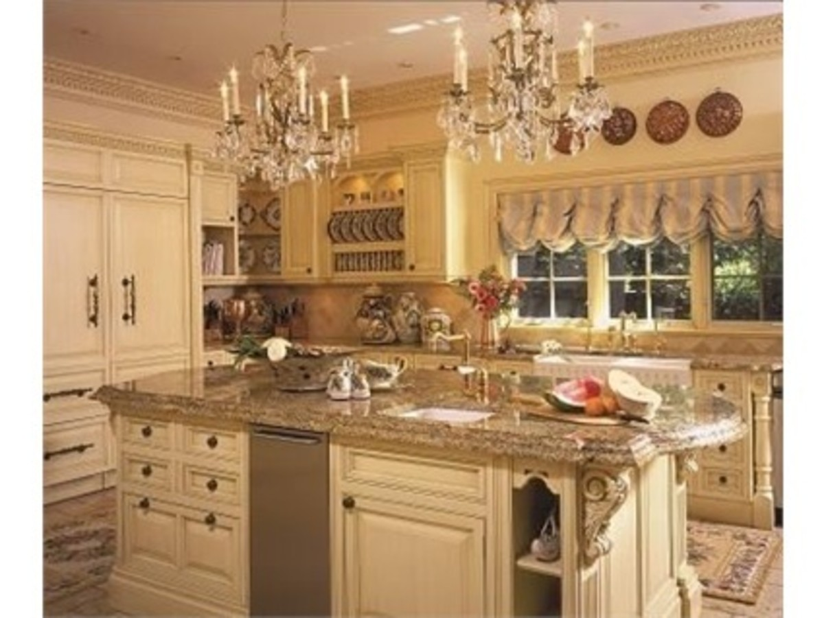 Old World design options showcased in glazed white kitchen cabinets with extensive moldings, plate racks and double chandeliers