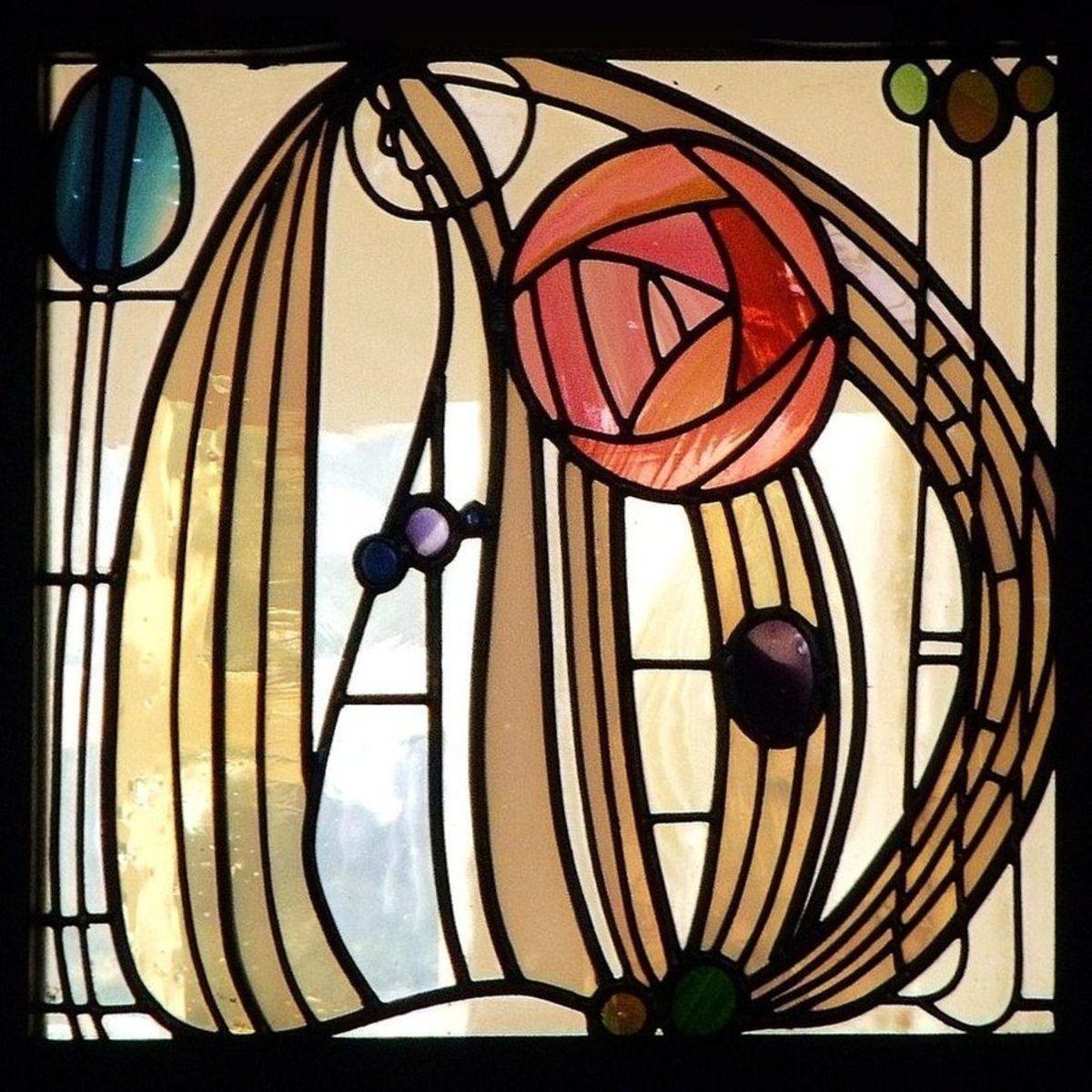 "Stained glass window from The Hill House, Glasgow by Charles Rennie Mackintosh, featuring his iconic ""Mackintosh Rose."""