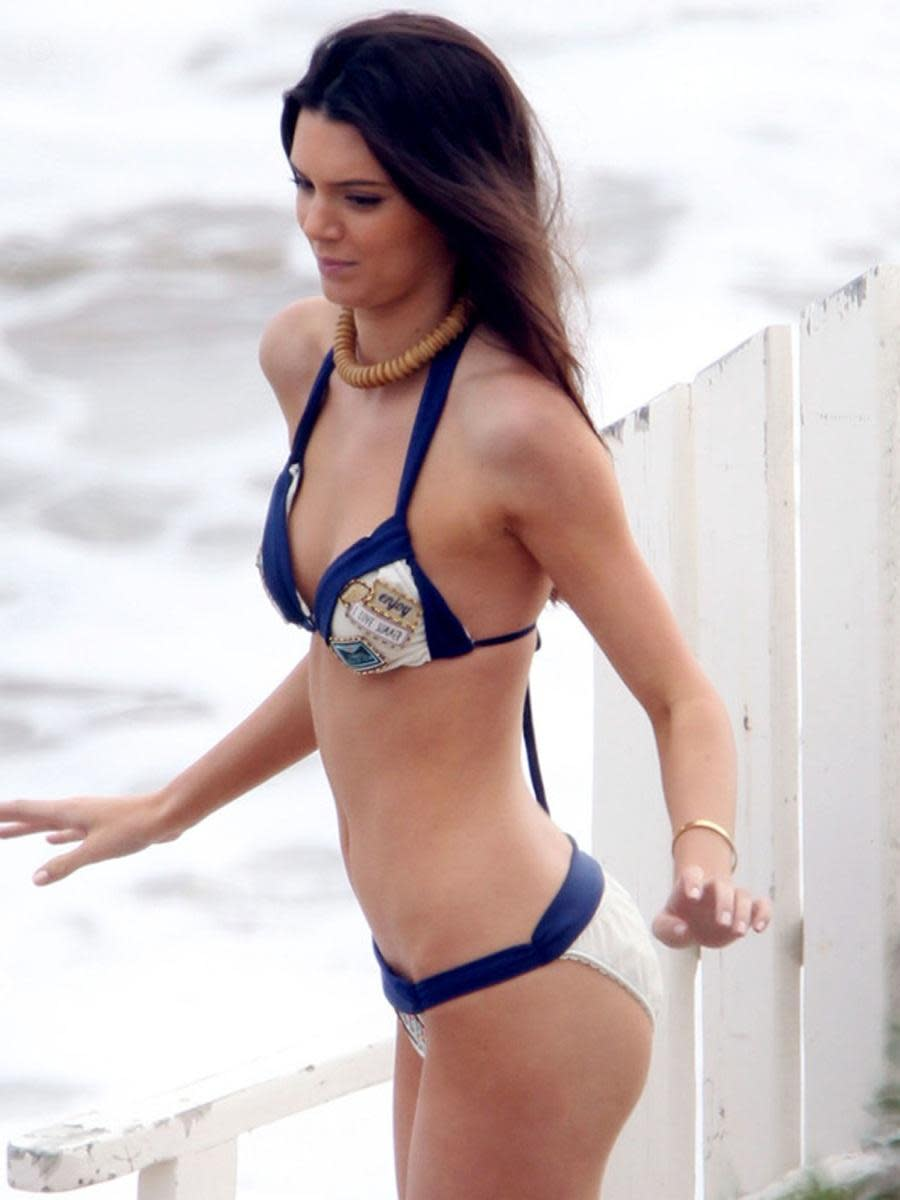 Kendall Jenner wears a wooden bead necklace and navy blue and white print bikini