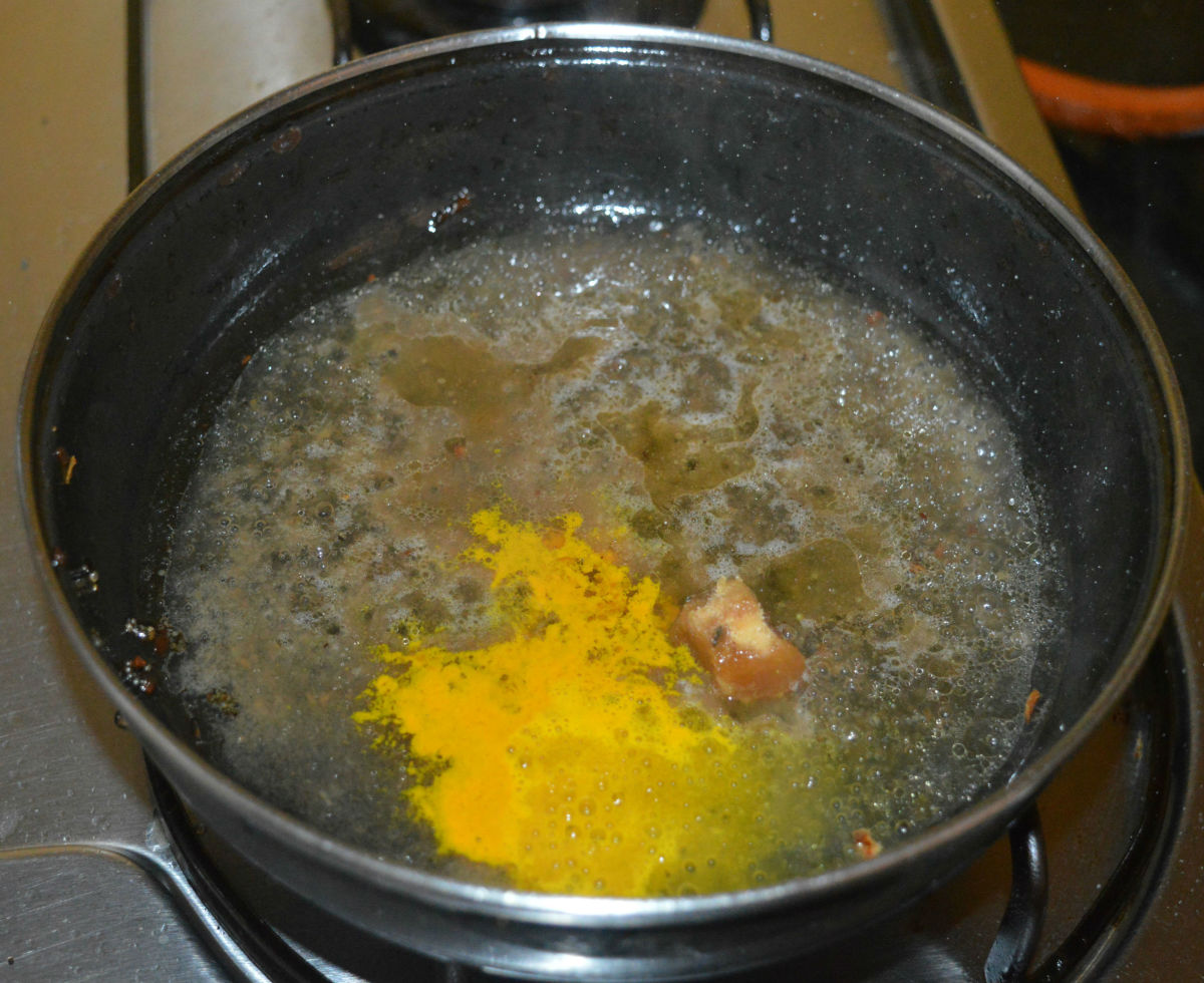 Step three: Heat the same pan once again. Add tamarind pulp, 1 cup of water, jaggery powder, and turmeric powder. Let the mixture come to a boil. Simmer for 1 minute.
