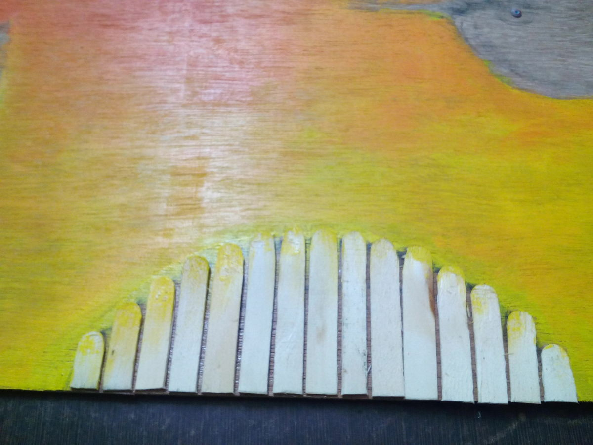 Ice cream sticks pasted to make the sun, keep painting thebackground as well in shades of orange and yellow