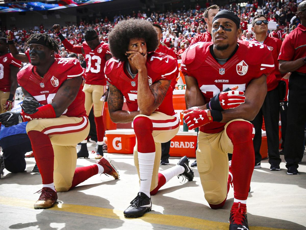 Taking a knee, during the playing of the National Anthem