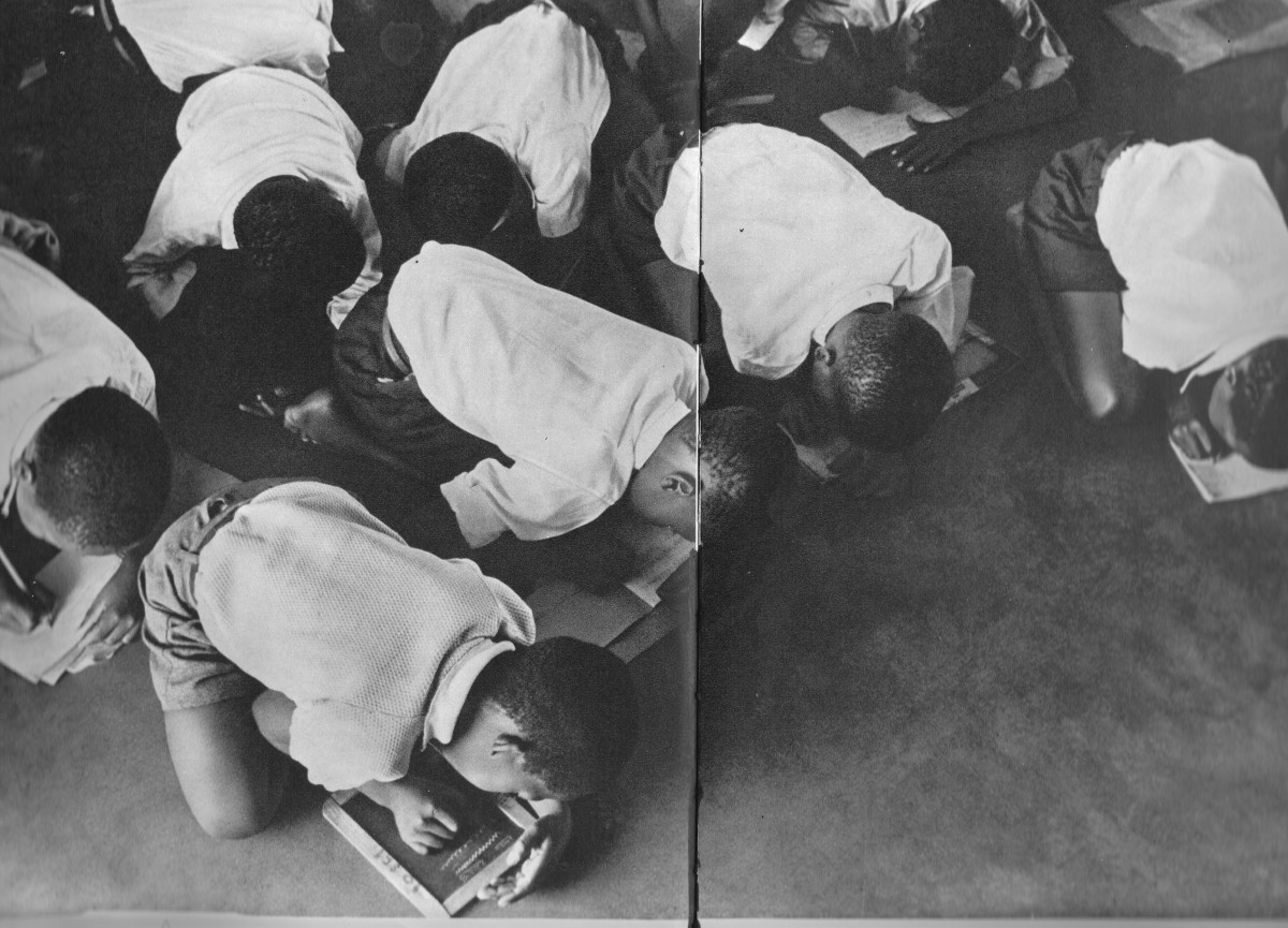 Students kneel on the floor to write. Government is casual and unwilling to furnish schools for Africans.
