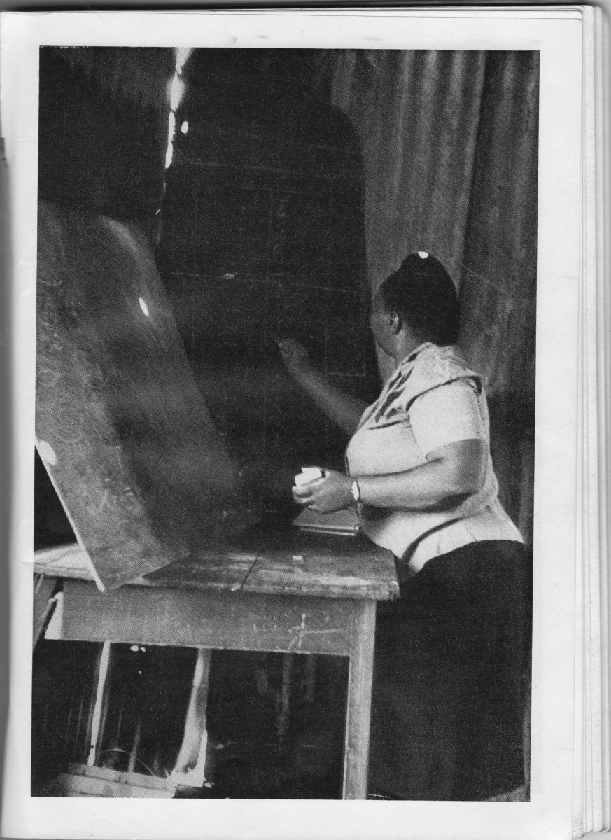 A teacher using two uneven Blackboards to write out the lesson's notes for her pupils, and the Blackboards are propped-up against the corrugated iron, and stood-up on a table. Photo #1, by Ernest L. Cole.