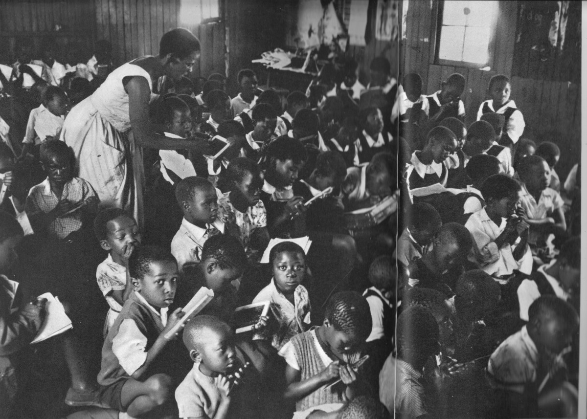 A teacher struggling with one of the two daily sessions of one hundred students each. Children learning to write hardly have elbow room to write on their slates and books