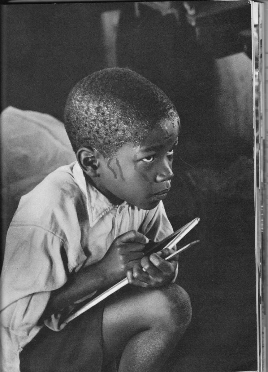 A pupil learning reading, writing and taking notes whilst earnestly squatting on haunches and straining to follow the lesson in the heat of a packed classroom