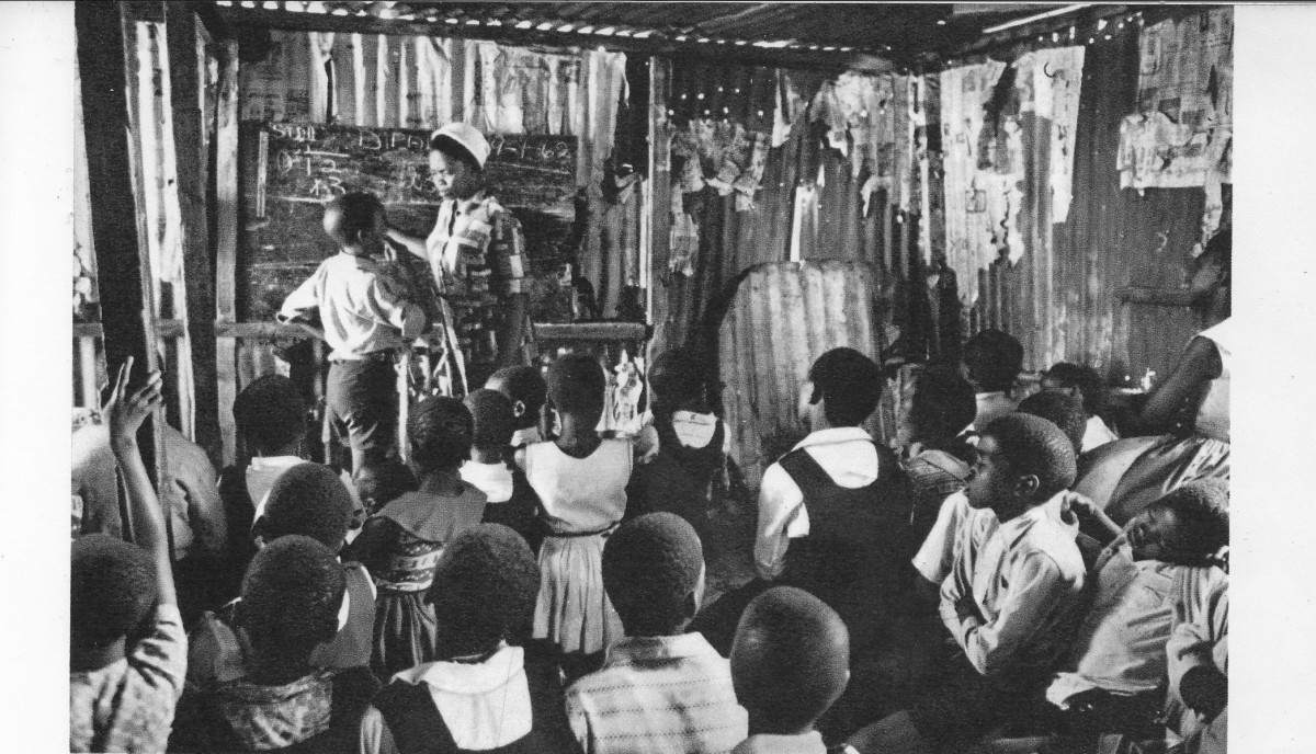 African children attending classes in any available structure, a tin shack, because of the shortage of school building. Parents and the township resident have to raise half the cost