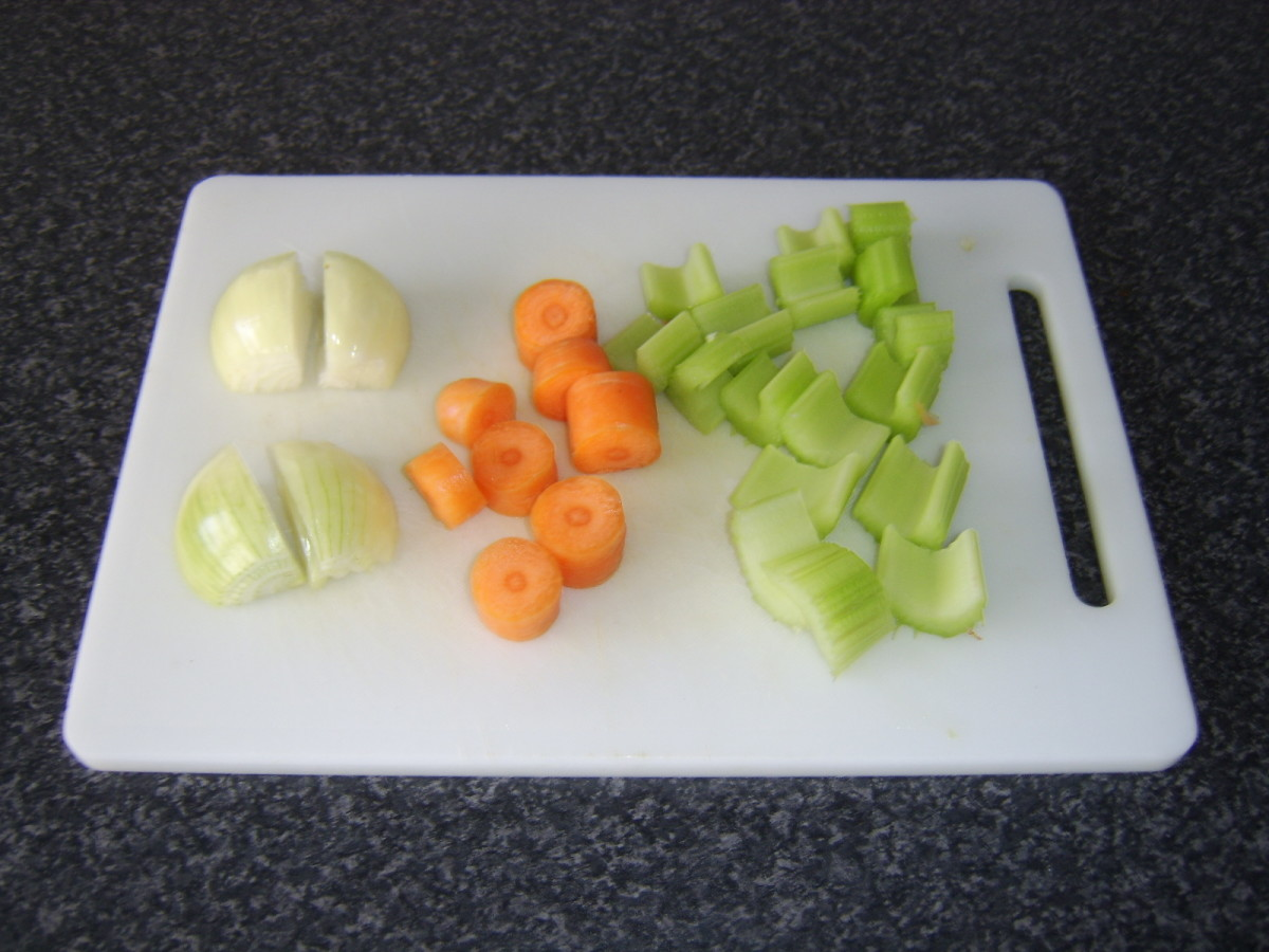 The onion, carrot and celery are roughly chopped in preparation for poaching the chicken